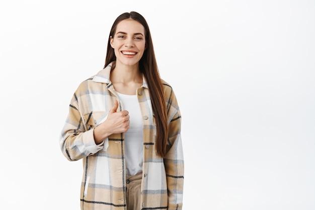 Uśmiechnięta zadowolona kobieta pokazuje kciuki z aprobatą i wygląda na zadowoloną i zadowoloną z przodu, chwali dobrą robotę, doskonały wybór, poleca coś dobrego, biała ściana