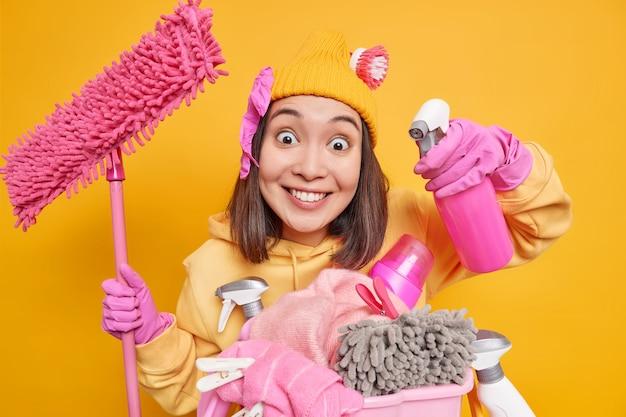 Uśmiechnięta, zadowolona, młoda azjatka trzyma butelkę z rozpylaczem i mop stoi w pobliżu kosza na pranie z butelkami chemicznymi, nosi gumowe rękawiczki, używa domu