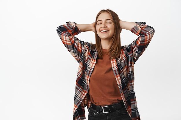 Uśmiechnięta zadowolona młoda kobieta odpoczywa, ma przerwę, trzyma ręce za głową i wzdycha z satysfakcją, relaksując się, stojąc przy białej ścianie