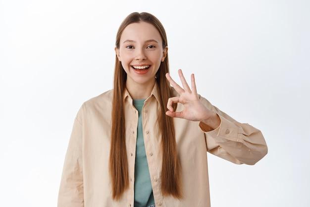 Uśmiechnięta zadowolona nastoletnia dziewczyna z naturalną długą fryzurą i nagim makijażem, pokazująca gest ok, kiwa głową z aprobatą, mówi tak, lubi i zgadza się, chwali doskonały wybór, biała ściana.
