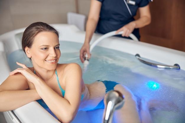 Uśmiechnięta zadowolona piękna młoda ciemnowłosa kobieta korzystająca z podwodnego masażu pod prysznicem w salonie spa