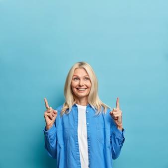 Uśmiechnięta zadowolona starsza kobieta o jasnych włosach ubrana w stylowe ubrania wskazuje powyżej na miejsce na reklamę