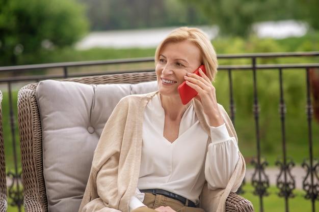 Uśmiechnięta zadowolona stylowa dama rozmawiająca przez telefon na zewnątrz