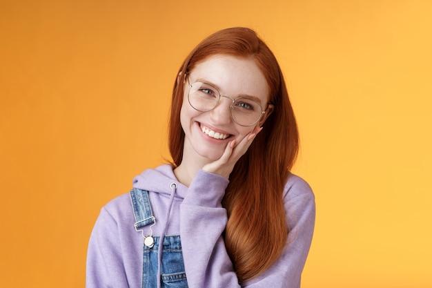 Uśmiechnięta zadowolona szczęśliwa rudowłosa dziewczyna pozbywa się trądziku zachwycona dotykając miękkiej czystej skóry śmiejąc się radośnie rozmawiając czuć pewność siebie pewność siebie piękna, stojąc pomarańczowe tło ciesz się komunikacją.
