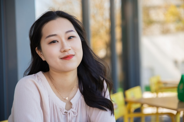 Uśmiechnięta zadumana azjatycka dziewczyna relaksuje w plenerowym sklep z kawą