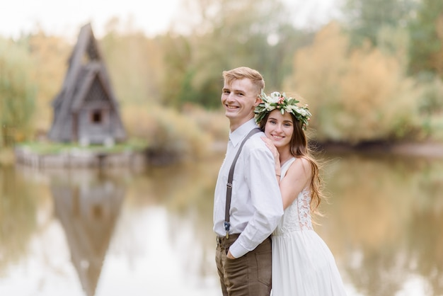 Uśmiechnięta zakochana para przytula się nad małym jeziorem, ubrana w przytulny strój ślubny w parku jesienią