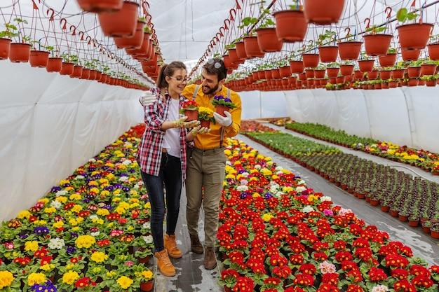 Uśmiechnięta zakochana para przytulająca się i trzymająca kwiaty podczas spaceru w szklarni
