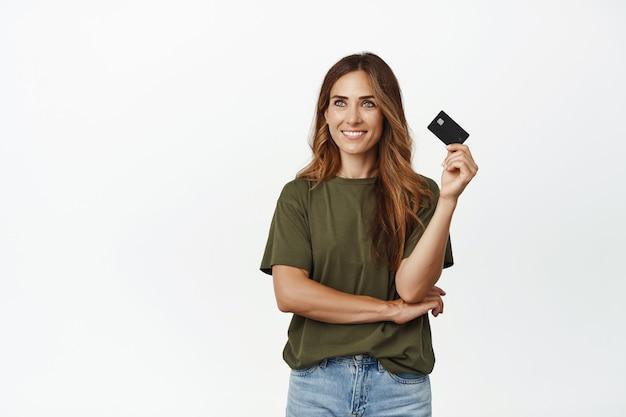 Uśmiechnięta zamyślona kobieta odwracająca wzrok, gotowa do użycia karty kredytowej