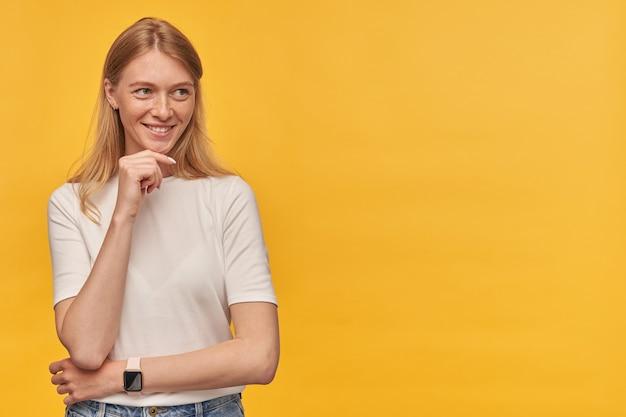 Uśmiechnięta zamyślona kobieta z piegami w białej koszulce trzyma ręce złożone i odwraca wzrok w pustą przestrzeń na żółto