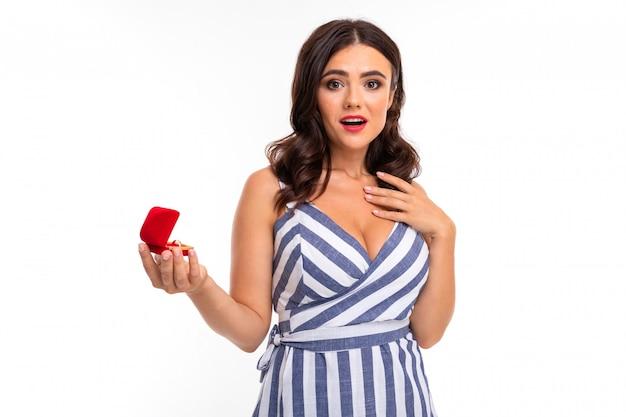 Uśmiechnięta zaskoczona młoda dziewczyna z brązowymi włosami w sukience z dekoltem wyciąga pudełko z pierścionkiem zaręczynowym w dłoniach