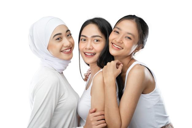 Uśmiechnięta zawoalowana dziewczyna i dwie młode azjatki śmiejące się i przytulające