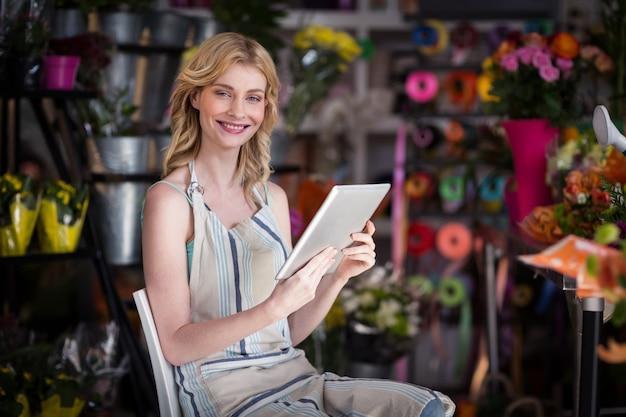 Uśmiechnięta żeńska kwiaciarnia używa cyfrową pastylkę w kwiaciarnia sklepie