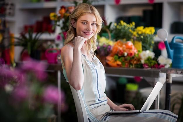 Uśmiechnięta żeńska kwiaciarnia używa laptop w kwiaciarnia sklepie