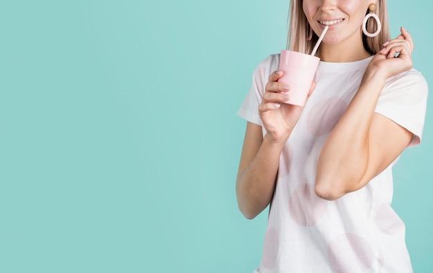 Uśmiechnięta żeńska popijanie napoju kopii przestrzeń