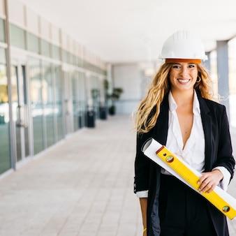 Uśmiechnięta żeński architekt z kasku