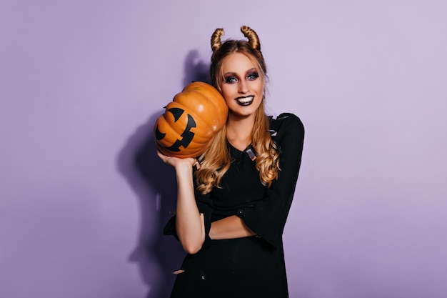 Uśmiechnięta zła czarownica pozowanie pod konfetti. elegancki blond wampir trzymając dyni i śmiejąc się.