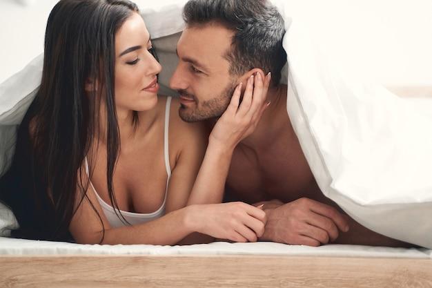 Uśmiechnięta żona i jej mąż patrzący sobie w oczy w łóżku pod kołdrą
