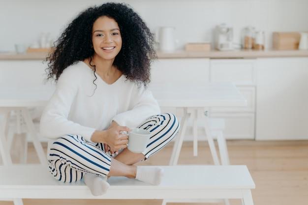 Uśmiechnięta zrelaksowana afroamerykanka siedzi skrzyżowane nogi na ławce przy kuchni, nosi biały sweter i spodnie w paski