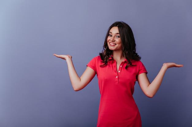 Uśmiechnięta zrelaksowana kobieta chce aparatu ze szczerym uśmiechem. zdjęcie zainteresowanej białej dziewczyny w stylowej sukience.