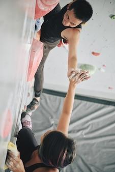 Uśmiechnięte atletki balansujące na sztucznych kamieniach na murku bulderowym i przybijające sobie piątki