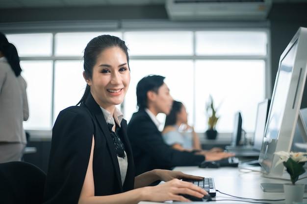 Uśmiechnięte biznesowe kobiety używają laptopa w biurze