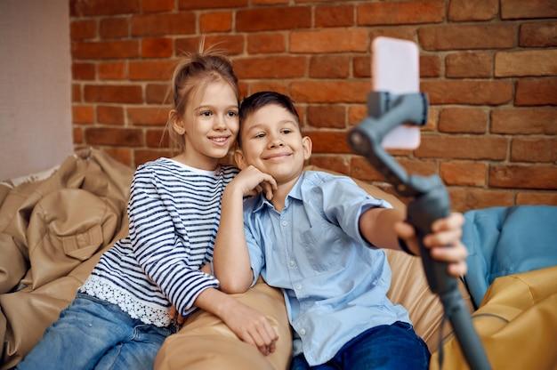 Uśmiechnięte blogerki dziecięce robią selfie na sofie, mali vlogerki. blogowanie dzieci w domowym studio, media społecznościowe dla młodych odbiorców, transmisja internetowa w internecie