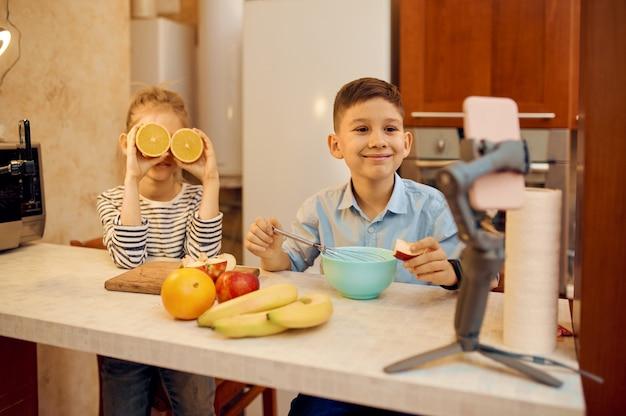 Uśmiechnięte blogerki dziecięce tworzą bloga kulinarnego, mali vlogerzy. blogowanie dzieci w domowym studio, media społecznościowe dla młodych odbiorców, transmisja internetowa w internecie