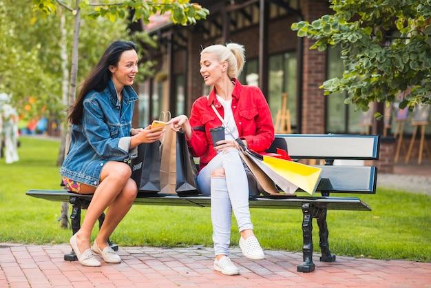 Uśmiechnięte damy patrzeje smartphone na ławce