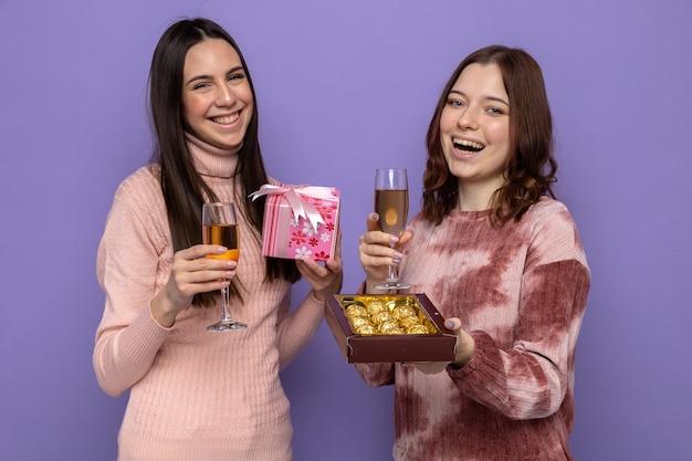 Uśmiechnięte dwie kobiety świętujące rocznicę z kieliszkami szampana, prezentem i pudełkiem cukierków