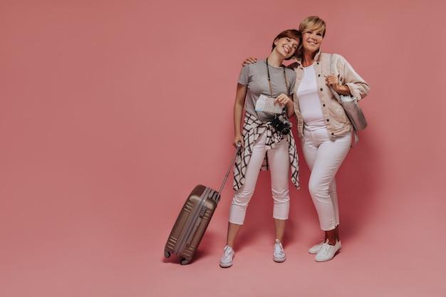Uśmiechnięte dwie kobiety z krótkimi fryzurami w trampkach i jasnych chudych spodniach, uśmiechnięte i pozujące z walizką, aparatem i dwoma biletami na różowym tle.