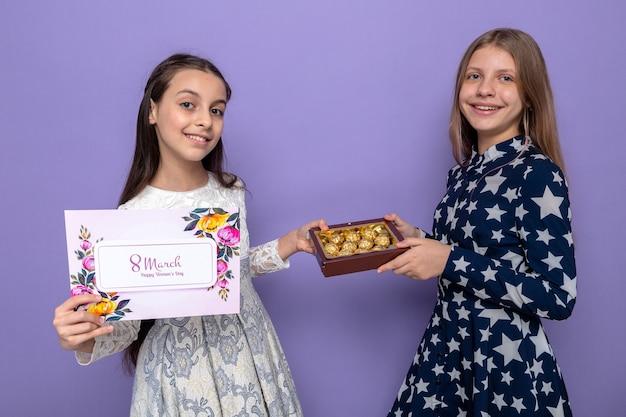 Uśmiechnięte dwie małe dziewczynki na szczęśliwy dzień kobiet trzymające kartkę z życzeniami z pudełkiem cukierków