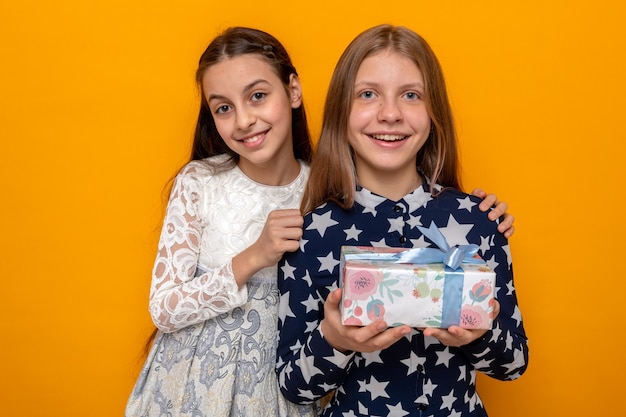 Uśmiechnięte dwie małe dziewczynki trzymające prezent