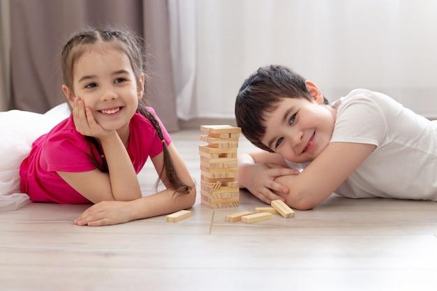 Uśmiechnięte dwoje dzieci grających w drewnianą grę na podłodze.