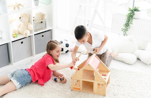 Uśmiechnięte dzieci bawiące się domkiem dla lalek