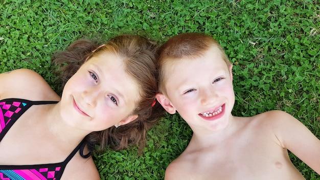 Uśmiechnięte dzieci r. na zielonej trawie