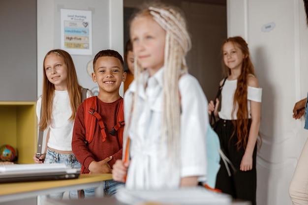 Uśmiechnięte dzieci stoją w klasie w szkole