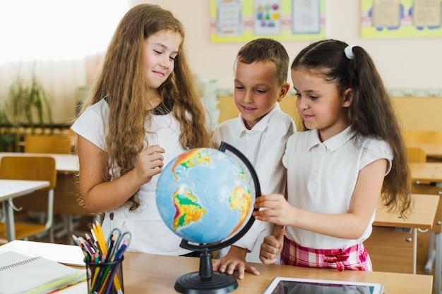Uśmiechnięte dzieci uczące się globu