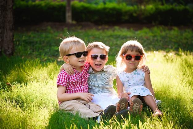 Uśmiechnięte dzieci w ogrodzie w okularach przeciwsłonecznych