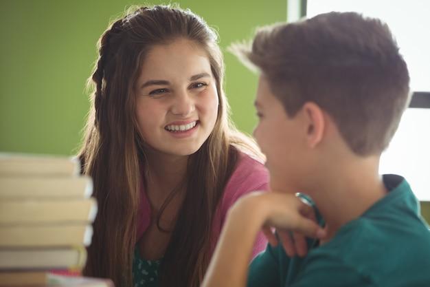 Uśmiechnięte dzieci w wieku szkolnym wchodzące w interakcje w bibliotece