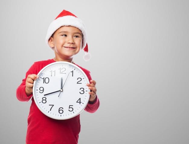 Uśmiechnięte dziecko chwytając zegar z rękami