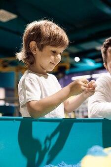 Uśmiechnięte dziecko czerpie przyjemność z zabawy piaskiem kinetycznym. terapia sztuką. łagodzenie stresu i napięcia. wrażenia dotykowe. rozwój umiejętności motorycznych. koncentracja i uwaga.