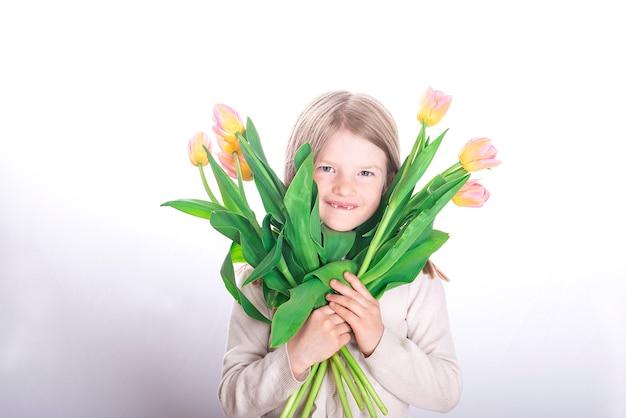 Uśmiechnięte dziecko dziewczynka bez przednich zębów trzymając kolorowe bukiety kwiatów tulipanów na białej powierzchni