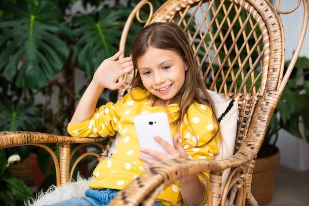 Uśmiechnięte dziecko dziewczynka komunikuje się online, siedząc na bujanym fotelu w domu