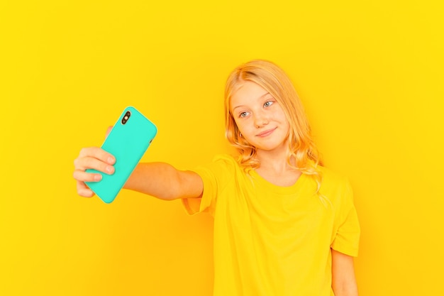 Uśmiechnięte dziecko dziewczynka pokazuje niebieski ekran nowego popularnego telefonu komórkowego na jasnożółtym tle.