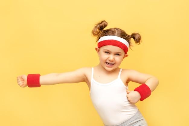 Uśmiechnięte dziecko fitness w odzieży sportowej na żółtej ścianie