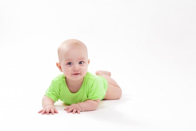 Uśmiechnięte dziecko leżące na brzuchu i patrząc