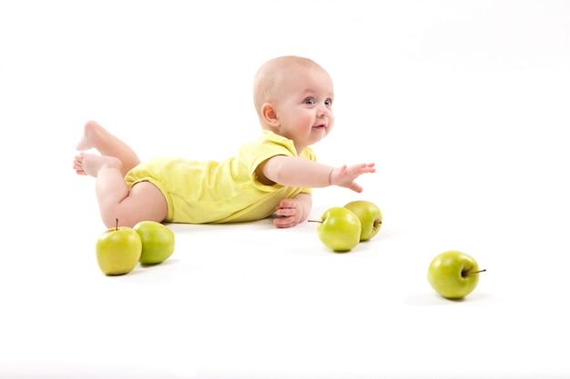 Uśmiechnięte dziecko leżące na ziemi, aby uwzględnić jabłka