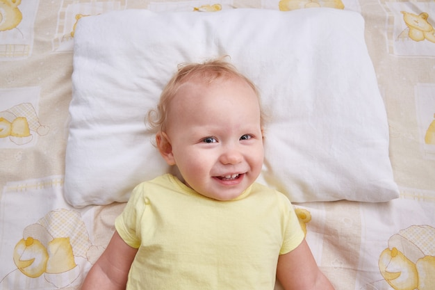 Uśmiechnięte dziecko leży na białej poduszce.