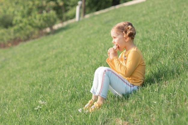 Uśmiechnięte dziecko na łonie natury je jedzenie, kanapki, chleb, piknik na świeżym powietrzu. kwarantanna się skończyła. koronawirus się skończył. zielona trawa i słoneczny letni tło. jedzenie i styl życia na świeżym powietrzu w przyrodzie.