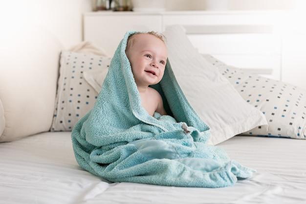 Uśmiechnięte dziecko okryte niebieskim ręcznikiem po kąpieli